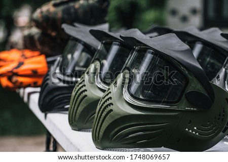 Closeup Photo of Paintball Gear Before Training At The Shooting Range. Protective Camouflage Mask at Table. Special protective mask for playing paintball Stock photo ©