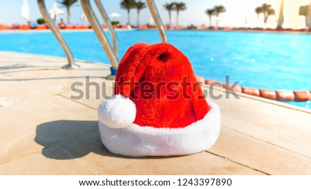 e241ba7776349 Closeup photo of red Santa Claus hat against swimming pool at bright sunny  day  1243397890