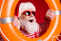 Closeup photo of retired grey beard old man hold inflatable circle open mouth newyear magic wear santa x-mas costume suspenders sunglass striped shirt cap isolated red color background