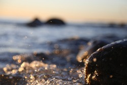 Closeup photo of sea waves braking on a wet seashore stones summer sunset, water splashes , sun rays, reflections on water drops.