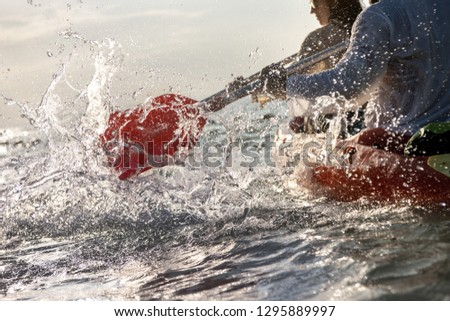 Closeup photo of splashes from kayak or canoe paddle at sea bay. Kayaking or canoeing concept