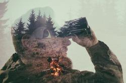 Closeup photo of stylish bearded traveler staring through binoculars. Double exposure, beautiful mountain landscape background. Made in vintage style.