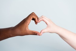 Closeup photo of two hands arms different race skin color multinational couple best friends anti racism issue help together showing heart figure love save world isolated grey background