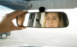 Closeup photo of woman adjusting car mirror and looking in the reflection