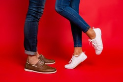 Closeup photo of woman and man legs in jeans, pants and shoes, girl with raised leg, stylish couple kissing during date, isolated over red background, he vs she