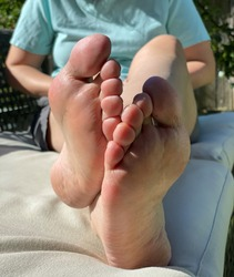 Closeup photo of woman crossed legs and soles lying on patio chair relaxing during summer