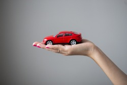 Closeup photo of woman hand holds a little car toy
