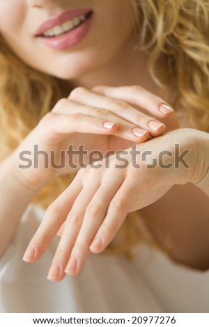 Closeup photo of woman hands applying creme