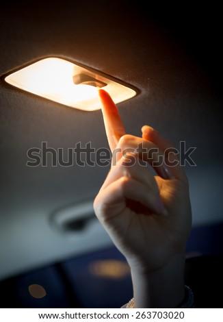 Closeup photo of woman turning light on in car salon