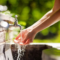 Closeup photo of woman washing hands in a city fountain