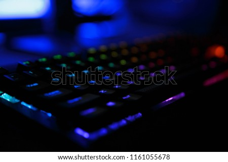 Closeup photo of workplace with led rainbow backlight gaming usb keyboard of computer lying on table in dark room