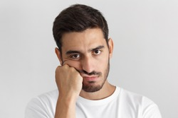 Closeup photo of young caucasian man isolated on gray background dressed casually, pressing hand to chin. looking bored, exhausted and disappointed, feeling helpless and upset, facing problems