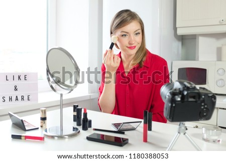 Closeup photo of young good-looking European girl pictured in her kitchen where she is filming beauty review of cosmetic products, applying powder to her skin with big soft brush, showing how to do