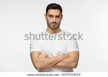 Closeup photo of young strong European Caucasian man pictured isolated on grey background dressed casually, standing with arms crossed and serious concentrated face at camera, looking aggressive