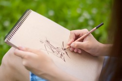 Closeup photo of young woman drawing with pencil on plain air, outdoors. Art education, talented students.