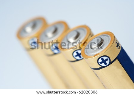 Closeup photo on small battery with positive and negative signs.