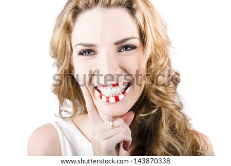 Closeup photo on the face of an adorable female cosmetics model laughing with red and white striped lips. Candy makeup
