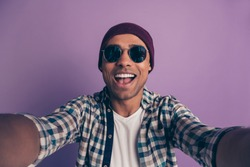 Closeup photo portrait of cheerful careless in white t-shirt plaid modern nice outfit blogger influencer instagram holding wed camera wirh hands making video call blogging isolated violet background