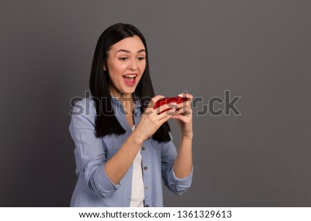 Closeup photo portrait of funky funky comic humorous screaming student using phone to play games, isolated gray background #1361329613