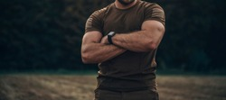 Closeup photo shoot of strong military man in army uniform with watch on his hand is standing crossed his hands.