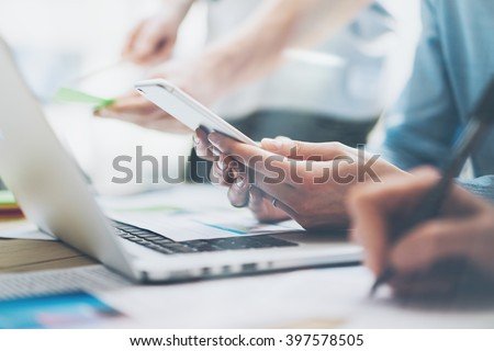 Closeup photo team job. Young business crew working with new startup project. Notebook on wood table,smartphone hands.Analyze plans, keyboard. Blurred background, film effect. Horizontal