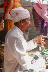 Closeup photograph of a Balinese Hindu high priest conducting a Ngaben ceremony in Ubud, Denpasar, Bali, Indonesia.