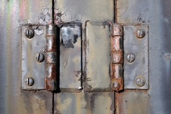 Closeup photograph of a pair of old rusty hinges from the engine bay of a 1940's American made  locomotive.