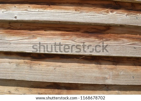 Closeup photograph of a stable wall made of overlapping pinewood planks. The photograph was taken on a sunny day. The planks are somewhat crooked, but more or less arranged horizontally. #1168678702