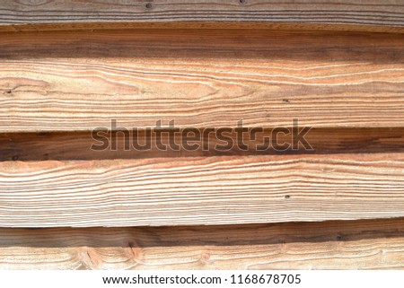 Closeup photograph of a stable wall made of overlapping pinewood planks. The photograph was taken on a sunny day. The planks are somewhat crooked, but more or less arranged horizontally. #1168678705