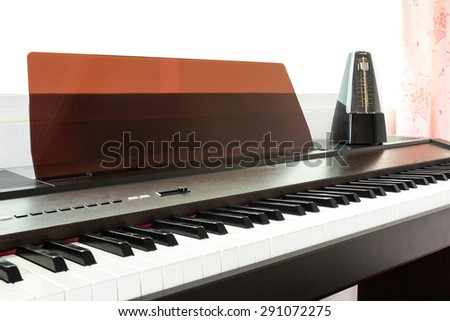 Closeup piano keyboard with metronome background. Abstract and art background.