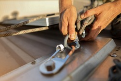 Closeup pic clipping Dynamic low stretch rope rigged with figure of eight knot into screwgate locking carabiner attached into industrial stainless abseiling fall arrest roof anchor point prior to used