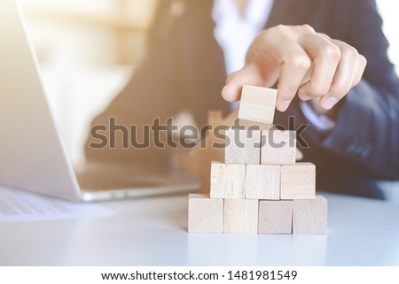 Closeup picture of a businessman placing wooden blocks to represent the peak of the boom to grow their business goals, financial statistics. #1481981549