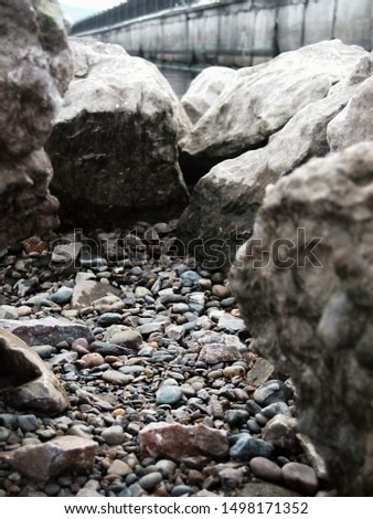 Closeup picture of a pile of grey stones with a lot of solid rocks around #1498171352