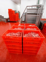 Closeup picture of a plastic red boxes with chopped fresh raw meat, worker arranged a stored in a meat factory.