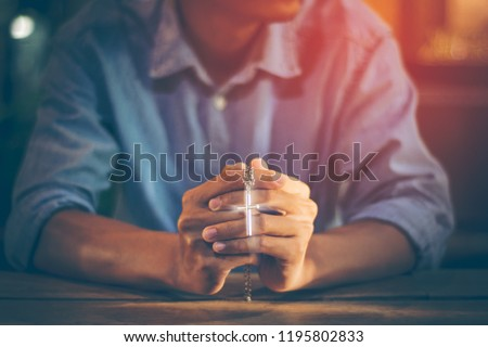 Closeup picture of a young Christian. He clasped hands and prayed God to bless the crucifix pendant, the symbol of the crucified Jesus by faith in Christ within the Catholic Church with copy space.