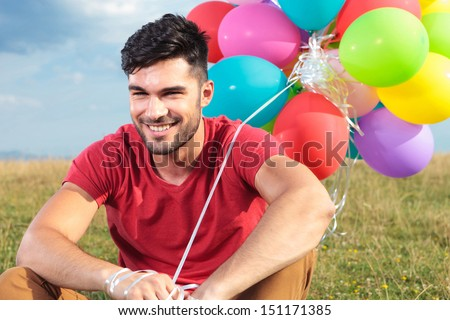 closeup picture of casual young man sitting outdoor on the grass and holding some balloons while smiling for the camera