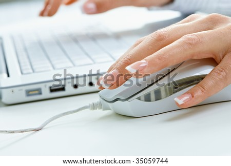 Closeup picture of computer keyboard and female hand using mouse.