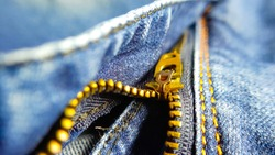 Closeup picture of denim zipper. Selective focus on the zipper. Stock image photography.