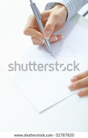 Closeup picture of female hand holding pen, drawing on paper.