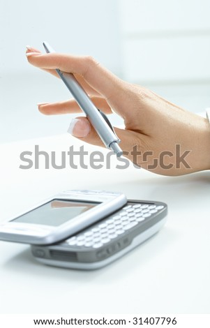 Closeup picture of female hand holding pen, using smart mobile phone.