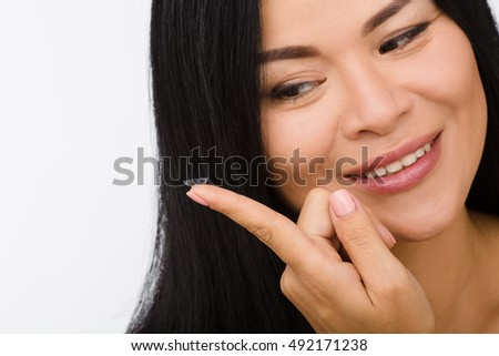 Closeup picture of happy smiling Korean or Asian woman looking at contact lens in front of her. Beauty, vision, eyesight, ophthalmology concepts. #492171238