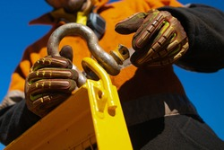 Closeup picture of rigger high risk worker wearing safety heavy duty glove, safety helmet fastening pin into D- shape shackle into crane lifting lug gate prior lift at construction site Perth city