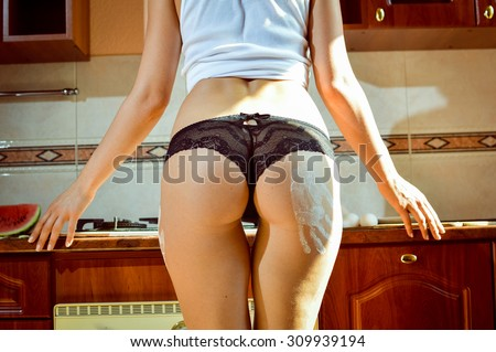 Closeup picture of sexy female model wearing black lace panties in kitchen. White flour handprint on hip.