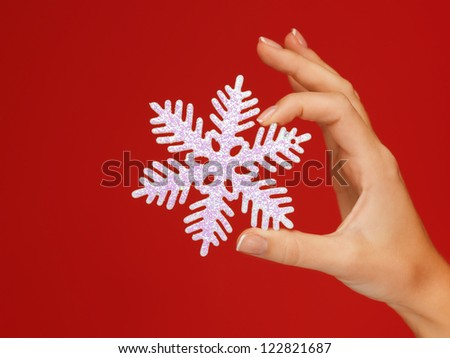 closeup picture of woman's hands holding a snowflake
