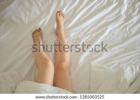 Closeup picture of woman's legs/feet on white clean bed sheet. There's only one sexy girl lying in comfortable bed. She just woke up in the morning. Lonely naked lady concept. Copy space given.
