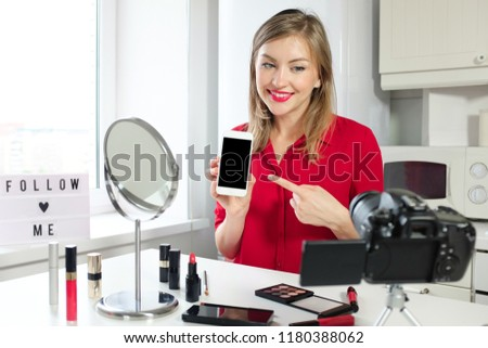 Closeup picture of young good-looking European female making video for her beauty channel, holding blank screen smartphone and pointing to it, recommending to use application or benefit from offer
