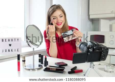 Closeup picture of young positive European female sitting at table with mirror and camera presenting nude eyeshadow palette to viewers pointing to some hues with brush to share her opinion about them
