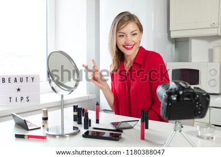 Closeup picture of young positive European female sitting at table with mirror and cosmetic products on it showing V sign with fingers as if greeting and welcoming viewers of her beauty channel