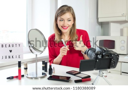 Closeup picture of young positive European Russian woman looking at camera, presenting metal stick of cosmetic product and talking about it to viewers of video blog about makeup and beauty, smiling