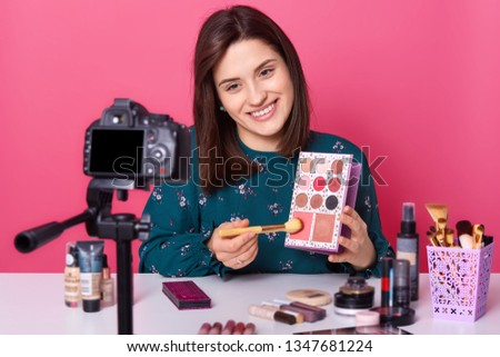 Closeup picture of young positive smiling European beauty vlogger sitting at table against camera and presents eyeshadow palette, makes tuturial video, broadcasting in social network. Beauty concept.